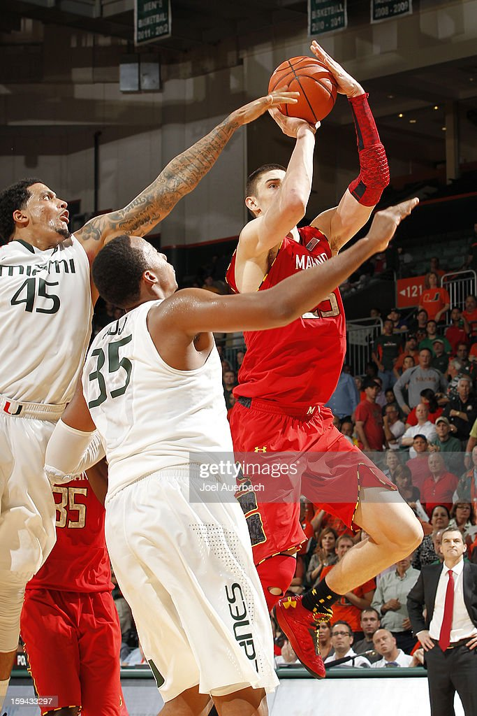 Alex Len #25 of the Maryland Terrapins goes to the basket past Kenny Kadji #35 and Julian Gamble #45 of the Miami Hurricanes on January 13, 2013 at the BankUnited Center in Coral Gables, Florida. Miami defeated Maryland 54-47.