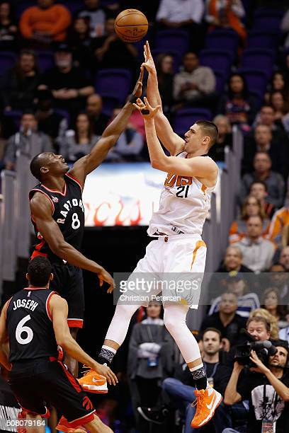 Alex Len of the Phoenix Suns attempts a shot over Bismack Biyombo of the Toronto Raptors during the first half of the NBA game at Talking Stick...