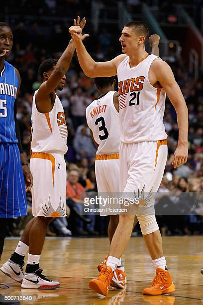 Alex Len of the Phoenix Suns highfives Ronnie Price after scoring against the Orlando Magic during the second half of the NBA game at Talking Stick...