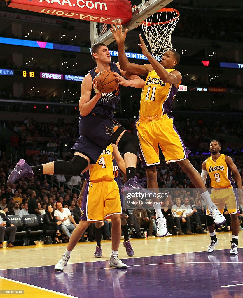 Alex Len #21 of the Phoenix Suns looks to make a pass play against Wesley Johnson #11 of the Los Angeles Lakers in the second period during the NBA game at Staples Center on November 4, 2014 in Los Angeles, California.