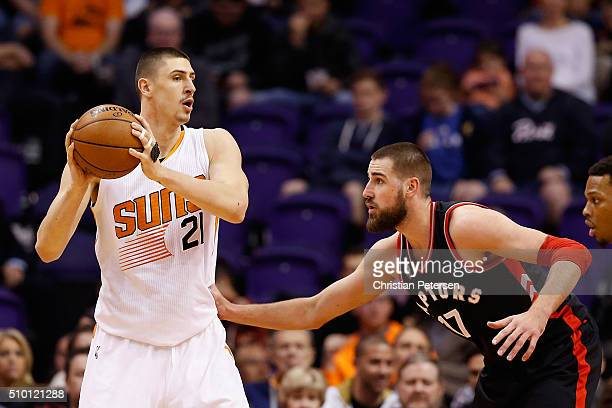 Alex Len of the Phoenix Suns looks to pass against Jonas Valanciunas of the Toronto Raptors during the NBA game at Talking Stick Resort Arena on...