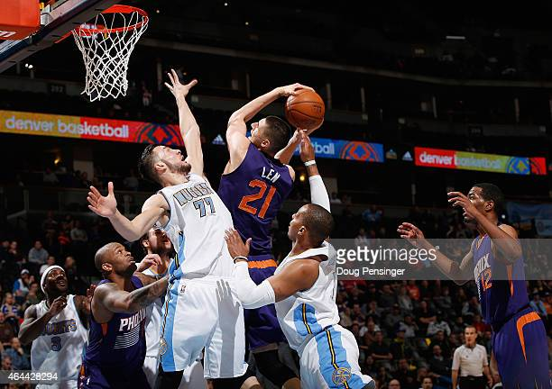 Alex Len of the Phoenix Suns tries to get off a shot against the defense of Joffrey Lauvergne and Randy Foye of the Denver Nuggets at Pepsi Center on...