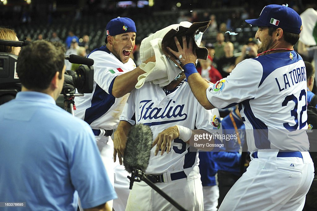 Alex Liddi #16 and and Tyler Latorre #32 of Team Italy hit teammate Chris Colabello #25 with a shaving cream pie after Pool D, Game 2 against Team Canada at Chase Field on Friday, March 8, 2013 in Phoenix, Arizona. Italy defeated Canada 14-4 in eight innings.