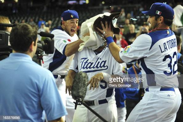 Alex Liddi and and Tyler Latorre of Team Italy hit teammate Chris Colabello with a shaving cream pie after Pool D Game 2 against Team Canada at Chase...