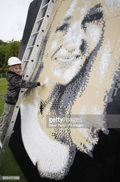 Alex Lindsey from Woolwich places the last of 48000 Lego bricks to create mosaic portrait of JK Rowling Legoland Windsor invited children to create a...