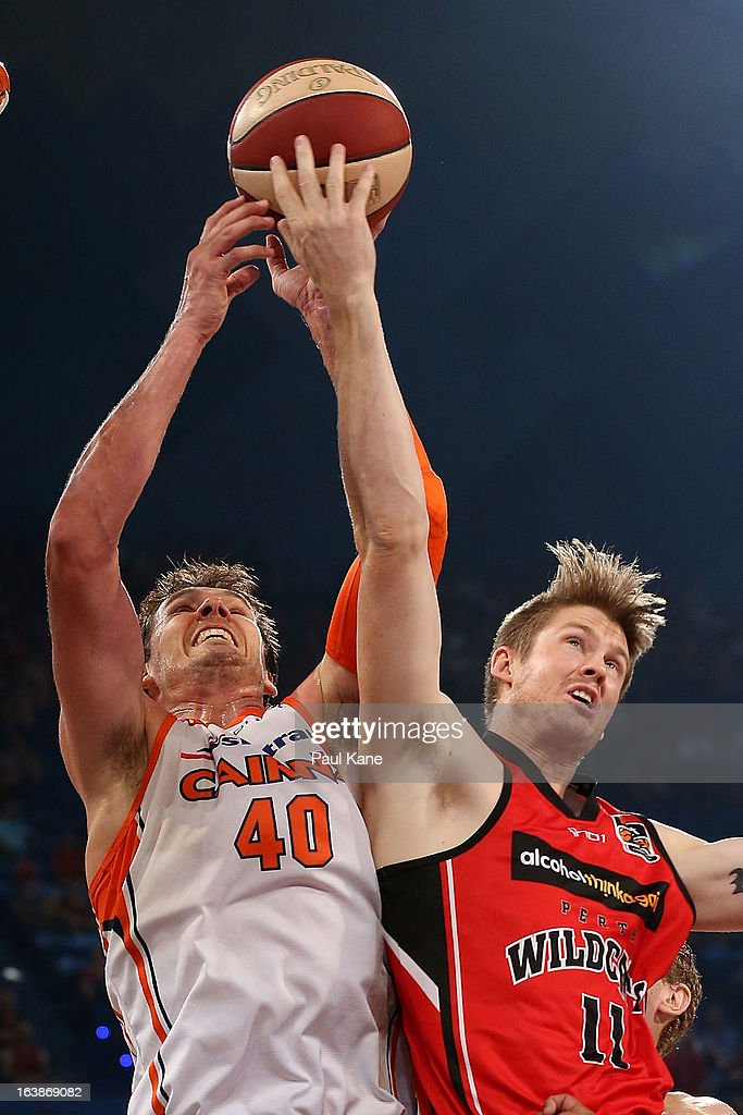 Alex Loughton of the Taipans and Cameron Tovey of the Wildcats contest for a rebound during the round 23 NBL match between the Perth Wildcats and the Cairns Taipans at Perth Arena on March 17, 2013 in Perth, Australia.