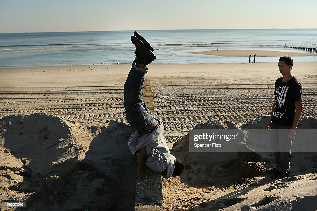 Alex Marin (right) and Bryant Blackshear practice 'parkour', a sport that embraces the urban landscape as an obstacle course, on the remains of the boardwalk at Rockaway beach on December 13, 2012 in New York City. Much of the Rockaway neighborhood is still suffering the effects of Hurricane Sandy which caused extensive damage to parts of New York, New Jersey and Connecticut. Thousands of Rockaway residents and business owners are still unable to return to their properties while electricity remains sporadic in many neighborhoods.