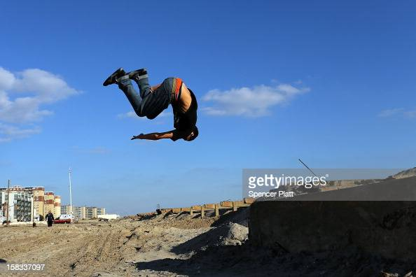Alex Marin practices 'parkour' a sport that embraces the urban landscape as an obstacle course on the remains of the boardwalk at Rockaway beach on...