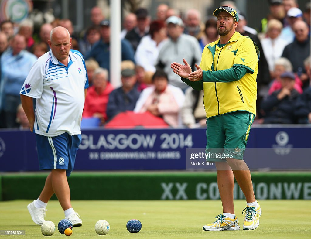 Alex Marshall of Scotland watches on as Matt Flapper of Australia congratulates his team mate during the men's fours semi-final match between Australia and Wales at Kelvingrove Lawn Bowls Centre during day eight of the Glasgow 2014 Commonwealth Games on July 31, 2014 in Glasgow, United Kingdom.