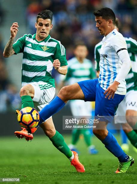 Alex Martinez of Real Betis Balompie competes for the ball with Pablo Fornals during La Liga match between Malaga CF and Real Betis Balompie at La...