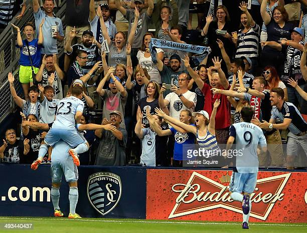 Alex Martinez of Sporting KC jumps on the back of Dom Dwyer after Dwyer scored the first of two goals during the game against the Toronto FC at...