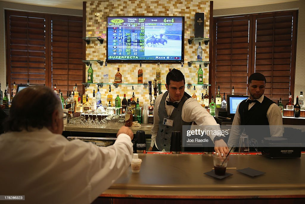 Alex Matos (L) and Jowar Hernandez work behind the bar in the casino that will hold its grand opening on Friday located in the Hialeah Park Race Track which first opened in 1925 on August 28, 2013 in Hialeah, Florida. The new casino is located in the same complex as the race track which in its heyday was known as the 'the worlds most beautiful race course.'