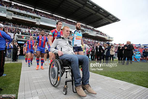 Alex McKinnon is wheeled onto the ground at before the start of the game during the round 19 NRL match between the Newcastle Knights and Gold Coast...