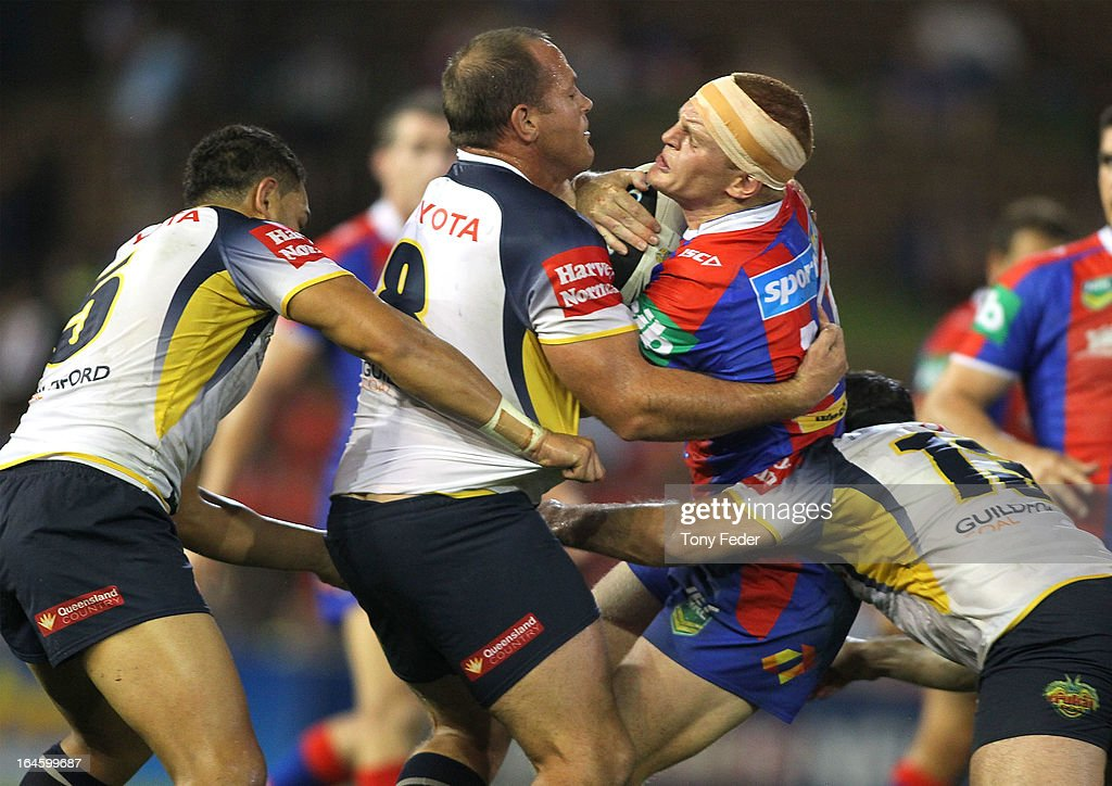 Alex McKinnon of the Knights is tackled by Antonio Winterstein and Matthew Scott of the Cowboys during the round three NRL match between the Newcastle Knights and the North Queensland Cowboys at Hunter Stadium on March 25, 2013 in Newcastle, Australia.