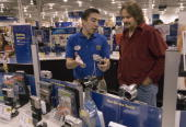 Alex Morenoleft shows Christmas Eve shopper Walter Leeright a digital camera at the Best Buy store in Corpus Christi Texas on Sunday December 24 2006...