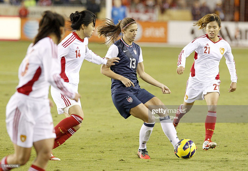 <a gi-track='captionPersonalityLinkClicked' href=/galleries/search?phrase=Alex+Morgan+-+Soccer+Player&family=editorial&specificpeople=1057310 ng-click='$event.stopPropagation()'>Alex Morgan</a> #13 of the U.S. Women's National Team kicks the ball away from Wang Dongni defender #14 of the China Women's National Team and Wang Lisi midfielder #21 of the China Women's National Team in an international friendly game on December 12, 2012 at BBVA Compass Stadium in Houston, Texas. USA won 4 to 0.