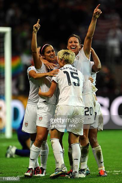 Alex Morgan of USA celebrates with team mate Abby Wambach and other team mates after scoring his teams first goal during the FIFA Women's World Cup...