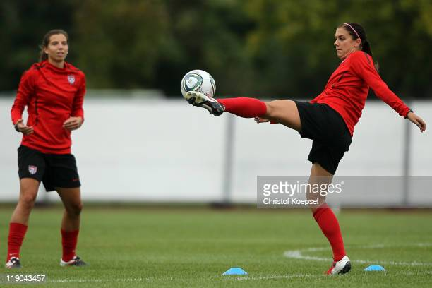 Alex Morgan shoots the ball at Tobin Heath of USA during the USA team training session at training ground Rebstock on July 14 2011 in Frankfurt am...