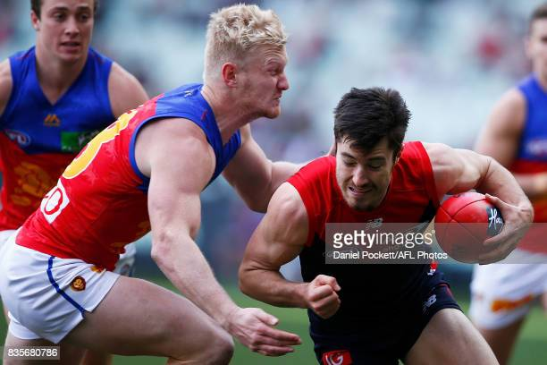 Alex NealBullen of the Demons is tackled by Nick Robertson of the Lions during the round 22 AFL match between the Melbourne Demons and the Brisbane...