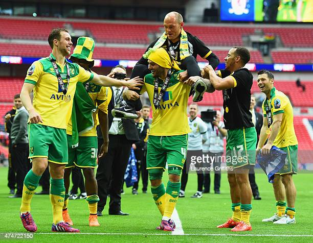 Alex Neil manager of Norwich City is carried by Bradley Johnson of Norwich City in celebration after the Sky Bet Championship Playoff Final between...