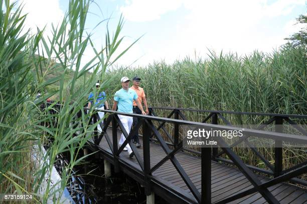 Alex Noren of Sweden and Haotong Li of China walk down the 16th hole during the final round of the Nedbank Golf Challenge at Gary Player CC on...