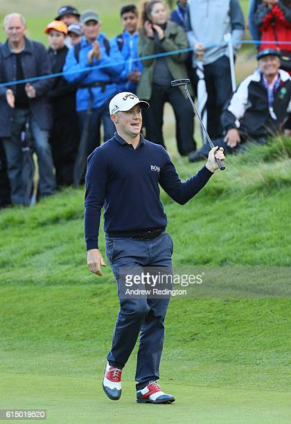 Alex Noren of Sweden celebrates after holing a birdie putt on the 15th green during the fourth round of the British Masters at The Grove on October...