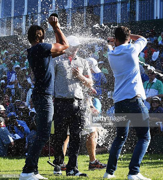 Alex Noren of Sweden celebrates winning as he is sprayed in champagne by Rikard Karlberg and Joakim Lagergren of Sweden after the final round of The...
