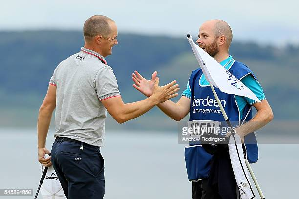 Alex Noren of Sweden celebrates with caddie Lee Warne after claiming victory on the 18th green during the final round of the AAM Scottish Open at...