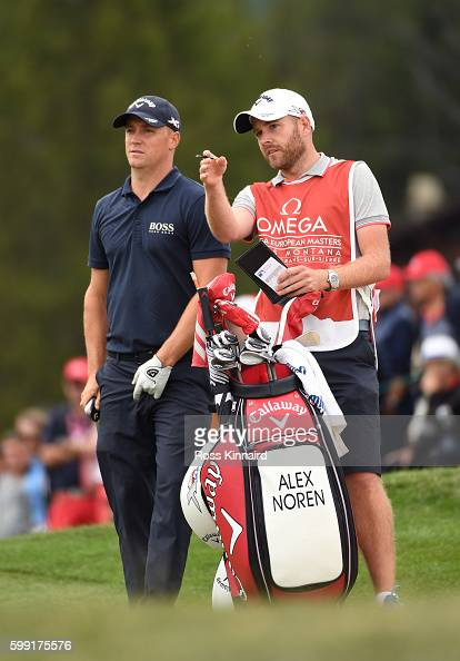 Alex Noren of Sweden consults with his caddy on the 12th hole during the final round of the Omega European Masters at CranssurSierre Golf Club on...