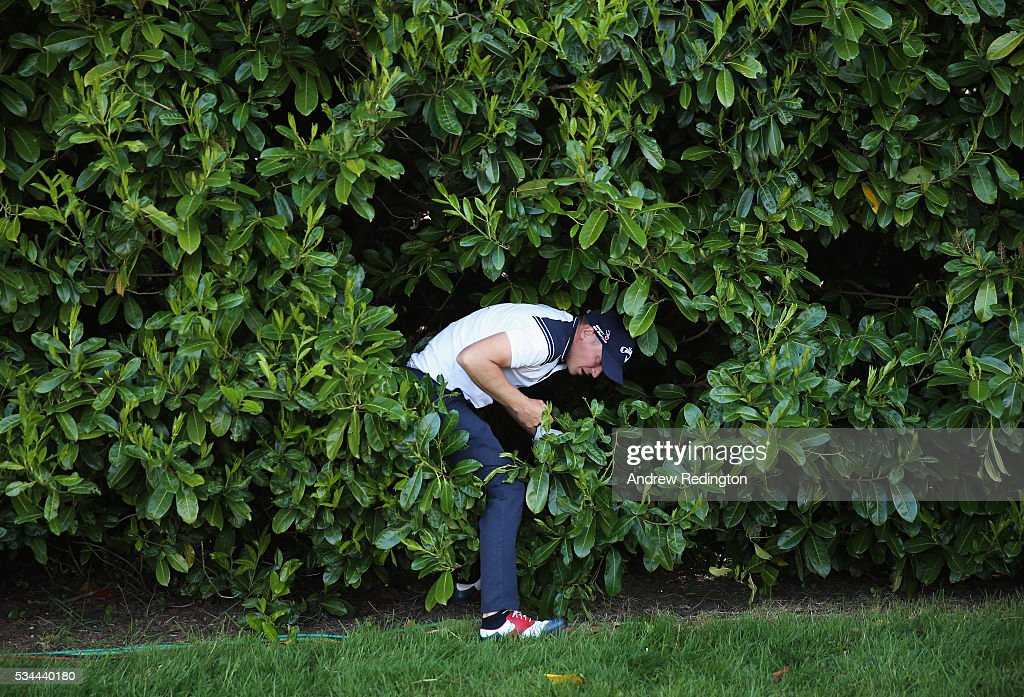 Alex Noren of Sweden emerges from the bushes on the 18th hole during day one of the BMW PGA Championship at Wentworth on May 26, 2016 in Virginia Water, England.