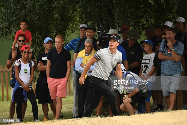 Alex Noren of Sweden reacts after playing his second shot on the 18th hole during the third round of the Omega European Masters at CranssurSierre...