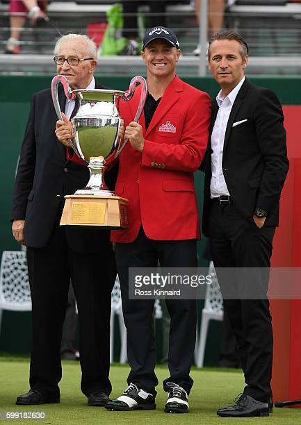 Alex Noren of Sweden receives the trophy folowing his victory during the final round of the Omega European Masters at CranssurSierre Golf Club on...