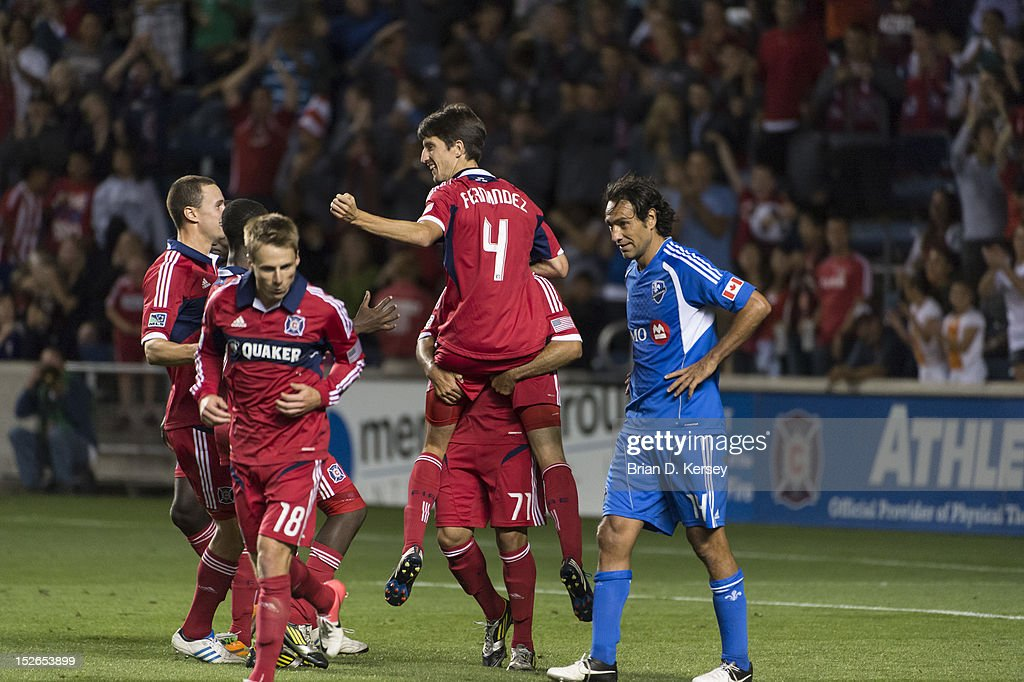 Alex #71 of Chicago Fire (C) picks up teammate Alvaro Fernandez #4 after Fernandez's goal as Alessandro Nesta #14 of Montreal Impact stands on the field at Toyota Park on September 15, 2012 in Bridgeview, Illinois. The Fire defeated the Impact 3-1.