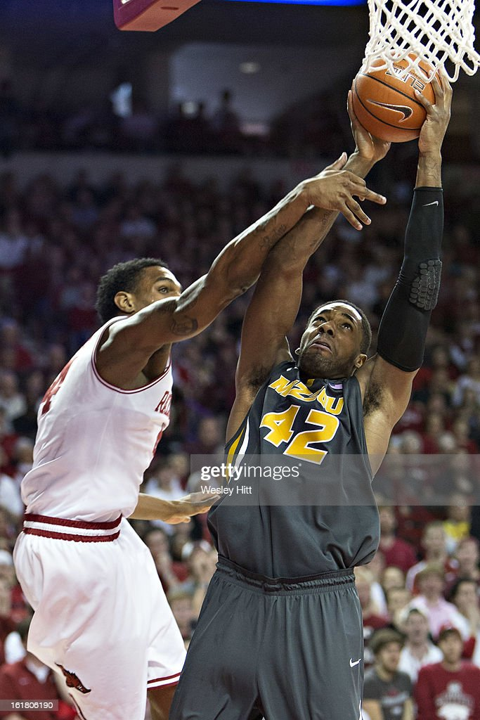 Alex Oriakhi #42 of the Missouri Tigers is fouled by Coty Clarke #4 of the Arkansas Razorbacks during the first half of the game at Bud Walton Arena on February 16, 2013 in Fayetteville, Arkansas.