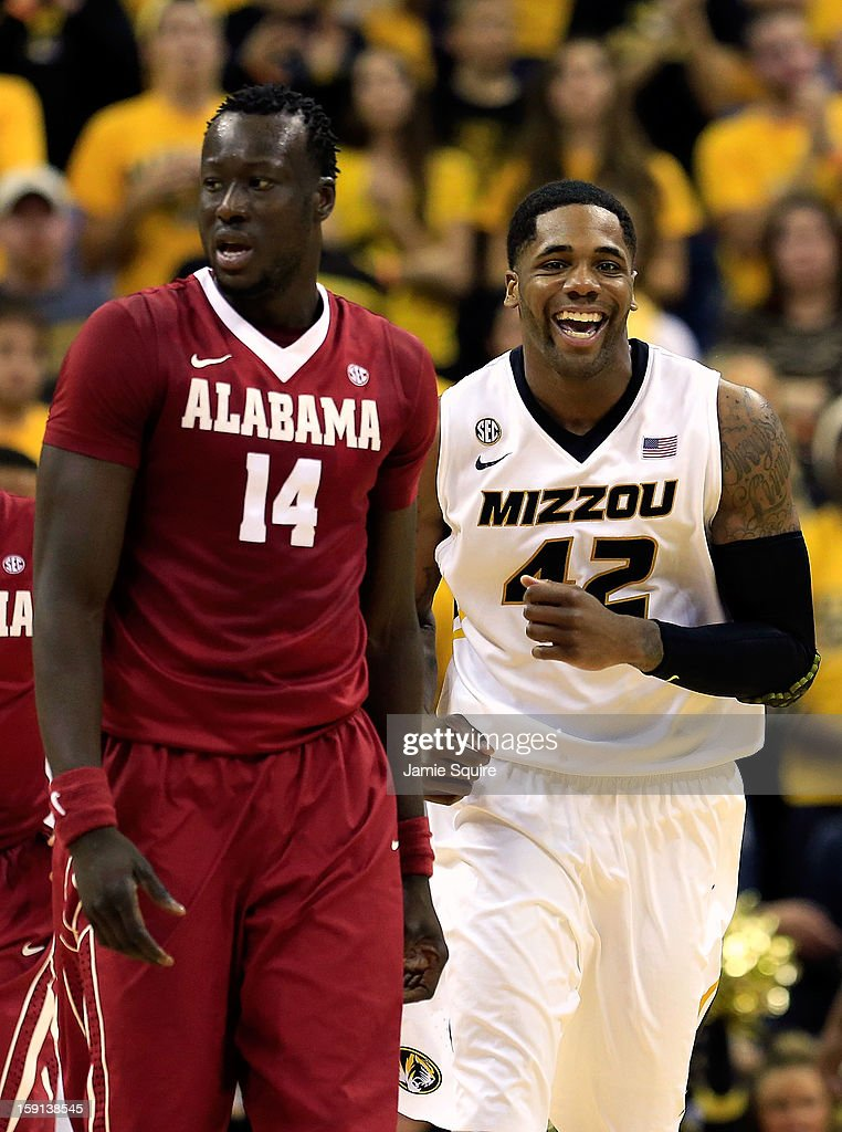 Alex Oriakhi #42 of the Missouri Tigers smiles as he passes Moussa Gueye #14 of the Alabama Crimson Tide after scoring during the game at Mizzou Arena on January 8, 2013 in Columbia, Missouri.