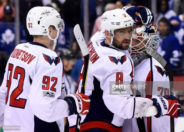 Alex Ovechkin and Evgeny Kuznetsov of the Washington Capitals congratulate their goaltender Braden Holtby after they defeated the Toronto Maple Leafs...