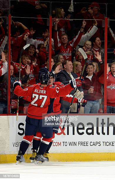 Alex Ovechkin celebrates with Karl Alzner of the Washington Capitals after scoring the game winning goal in overtime during an NHL game against the...