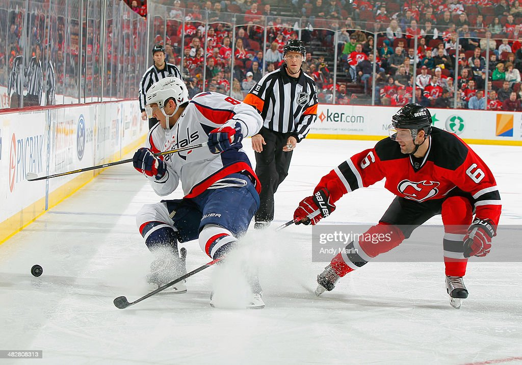 Alex Ovechkin #8 of the Washington Capitals and Andy Greene #6 of the New Jersey Devils battle for position on a loose puck during the game at the Prudential Center on April 4, 2014 in Newark, New Jersey