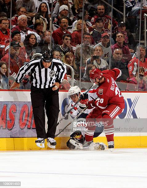 Alex Ovechkin of the Washington Capitals and Eric Belanger of the Phoenix Coyotes fight for control of the puck as it gets caught up in the skates of...