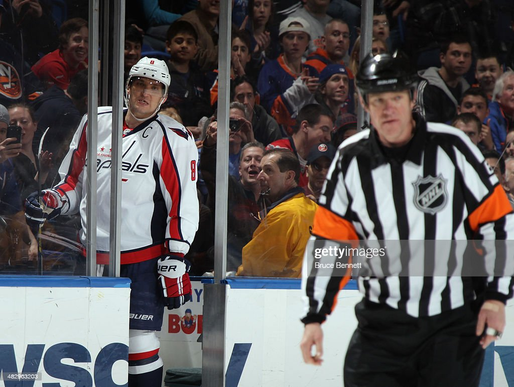 Alex Ovechkin #8 of the Washington Capitals argues his two minute roughing against the New York Islanders with referee Dave Jackson #8 at the Nassau Veterans Memorial Coliseum on April 5, 2014 in Uniondale, New York.