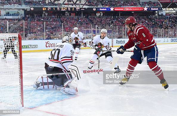 Alex Ovechkin of the Washington Capitals bats the puck as goaltender Corey Crawford of the Chicago Blackhawks defends his net in the second period...