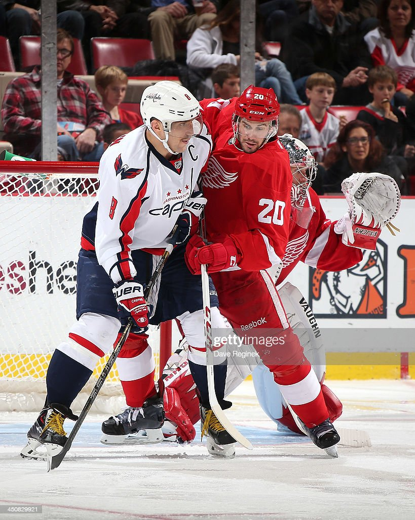 Alex Ovechkin #8 of the Washington Capitals battles for position with Drew Miller #20 of the Detroit Red Wings during an NHL game at Joe Louis Arena on November 15, 2013 in Detroit, Michigan. The Capitals defeated the Wings 4-3 in OT