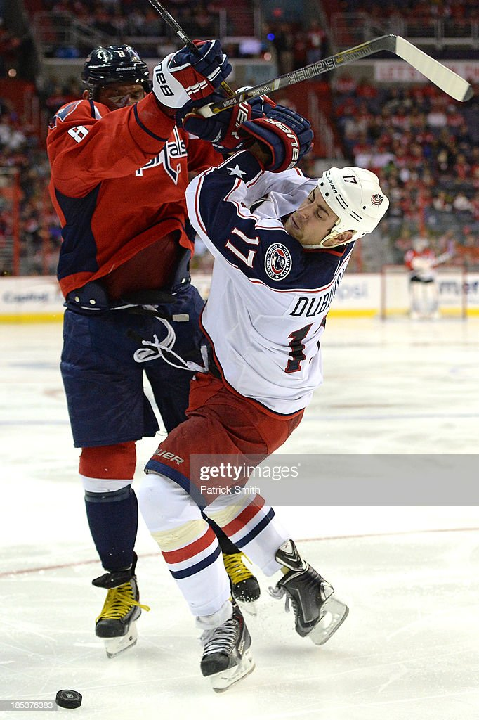 Alex Ovechkin #8 of the Washington Capitals body checks <a gi-track='captionPersonalityLinkClicked' href=/galleries/search?phrase=Brandon+Dubinsky&family=editorial&specificpeople=2271907 ng-click='$event.stopPropagation()'>Brandon Dubinsky</a> #17 of the Columbus Blue Jackets in the third period at the Verizon Center on October 19, 2013 in Washington, DC.