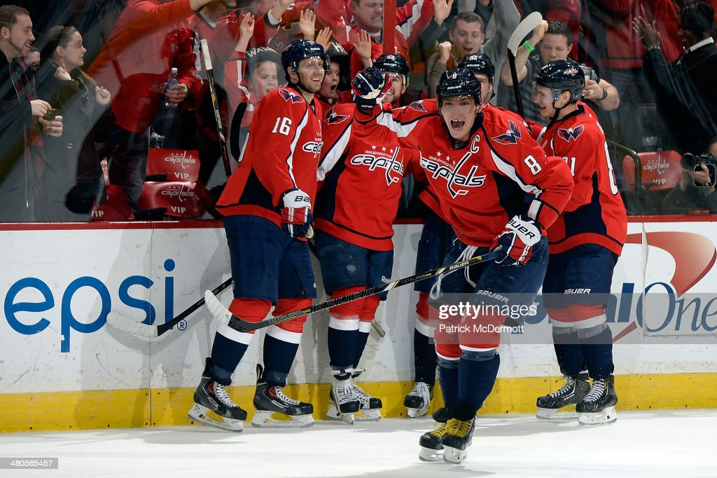 Alex Ovechkin #8 of the Washington Capitals celebrates after Evgeny Kuznetsov #92 scored his first career NHL goal in the third period during an NHL game against the Los Angeles Kings at Verizon Center on March 25, 2014 in Washington, DC.