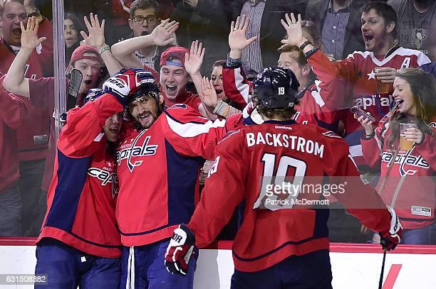 Alex Ovechkin of the Washington Capitals celebrates with TJ Oshie and Nicklas Backstrom after scoring a goal for his 1000th career point against the...