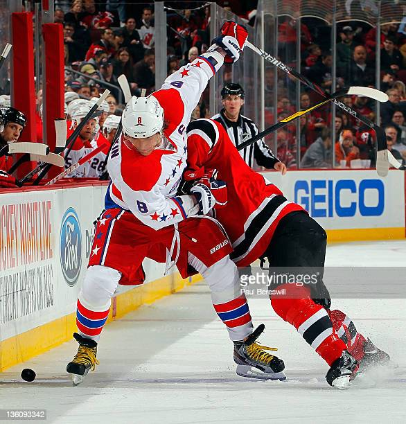 Alex Ovechkin of the Washington Capitals eludes a check by Bryce Salvador of the New Jersey Devils during the third period of an NHL hockey game at...