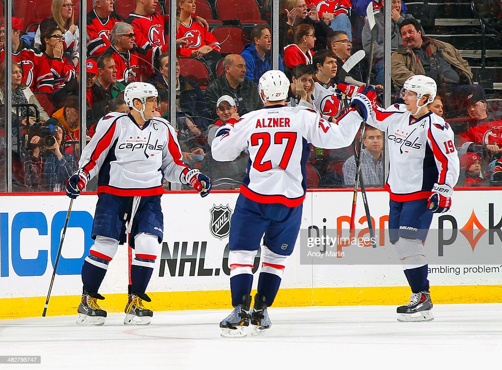 Alex Ovechkin #8 of the Washington Capitals is congratulated by teammates Karl Alzner #27 and Nicklas Backstrom #19 after scoring a first-period goal against the New Jersey Devils during the game at the Prudential Center on April 4, 2014 in Newark, New Jersey.