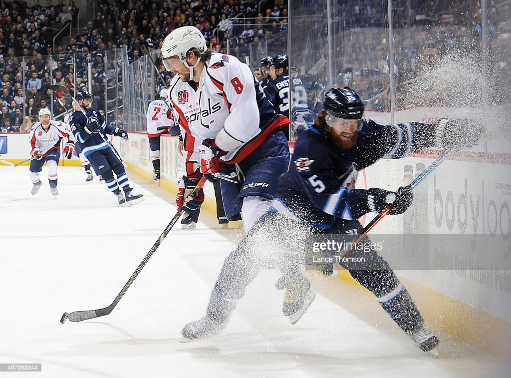 Alex Ovechkin of the Washington Capitals jumps past a checking Matt Halischuk of the Winnipeg Jets during third period action on March 21 2015 at the...