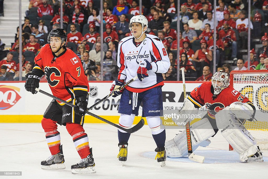 Alex Ovechkin #8 of the Washington Capitals looks for an opportunity as T.J. Brodie #7 and Karri Ramo #31 of the Calgary Flames defend during an NHL game at Scotiabank Saddledome on October 26, 2013 in Calgary, Alberta, Canada.