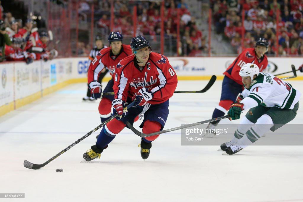 Alex Ovechkin #8 of the Washington Capitals moves the puck in front of <a gi-track='captionPersonalityLinkClicked' href=/galleries/search?phrase=Kyle+Brodziak&family=editorial&specificpeople=2165412 ng-click='$event.stopPropagation()'>Kyle Brodziak</a> #21 of the Minnesota Wild during the third period of the Capitals 3-2 shootout win at Verizon Center on November 7, 2013 in Washington, DC.